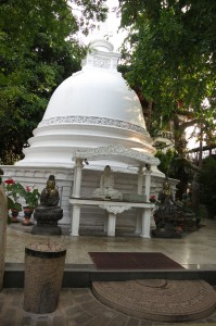 Coral-white stupa and serene Buddha statues on tranquil temple grounds