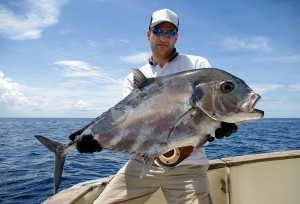 Big game fishing man holding a trevally jack